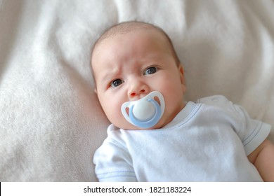 Headshot portrait of cute newborn baby lying on bed with pacifier on mouth. Mixed race Asian-German infant boy.