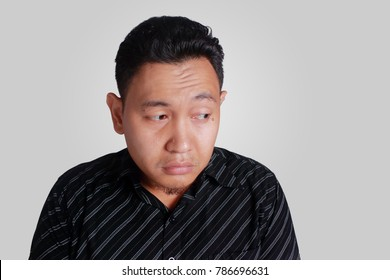 Headshot portrait of funny young Asian man showing cute sad facial expression, isolated on grey