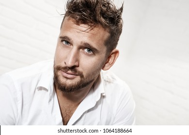 Headshot portrait of handsome casual man against white brick background.