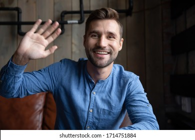 Headshot portrait of happy Caucasian young man sit in cafe wave greeting talking on video call, smiling millennial male have fun speaking online using gadget engaged in internet dating service