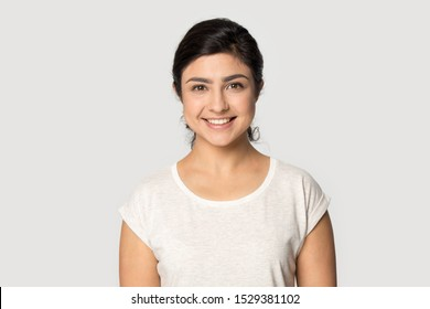 Headshot portrait of happy indian millennial girl stand isolated on grey studio background wear t-shirt look at camera, smiling ethnic young woman posing showing white healthy teeth, dental treatment