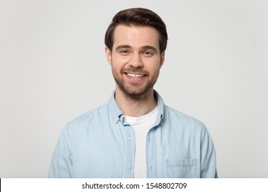 Headshot portrait of happy millennial man in casual clothes isolated on grey studio background posing, smiling young male in shirt look at camera with wide healthy teeth, demonstrated dental treatment - Shutterstock ID 1548802709