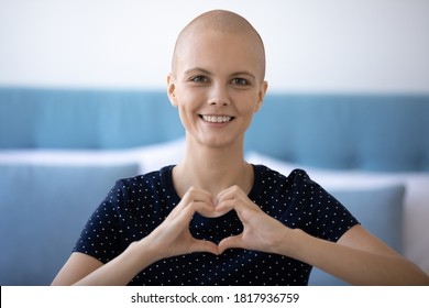 Headshot portrait of happy young hairless woman beat cancer look at camera show heart love gesture sign with hands. Smiling bald female oncology patient feel optimistic support sick people, volunteer.