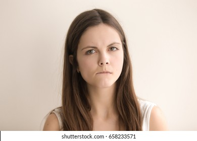 Headshot portrait of nervous confused young woman. Worried teenager girl biting lip and looking at camera with sadness, doubts in decision. Stressed female thinking about problem. Close up. Front view