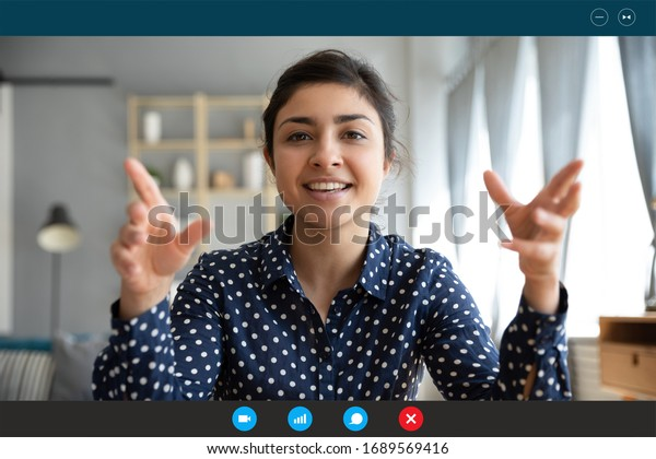 Headshot portrait screen view of smiling young Indian woman sit at home talk on video call with friend or relative, happy millennial biracial female speak online using Webcam conference on computer