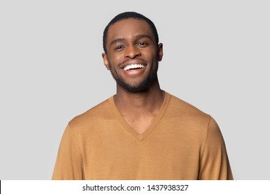 Headshot portrait of smiling african American millennial man in tshirt isolated on grey studio background, happy black male look at camera feel satisfied or pleased laughing posing for picture