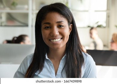 Headshot portrait of smiling African American female employee have video call or web conference in office, profile picture of happy biracial woman worker posing look at camera in coworking space
