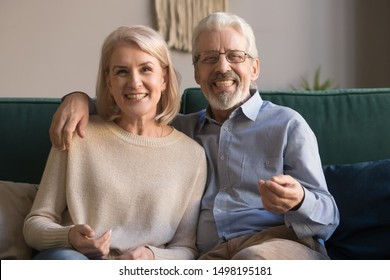 Headshot portrait of smiling elderly husband and wife feel positive overjoyed sit on couch at home, happy mature spouses couple look at camera talk on video call on computer, use new technologies
