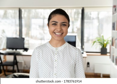 Headshot portrait of smiling indian female employee look at camera pose in office, profile picture of happy millennial biracial woman worker show confidence success at workplace, leadership concept