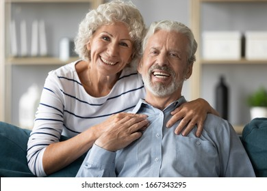 Headshot portrait of smiling middle-aged 60s husband and wife sit relax on couch at home look at camera posing, happy elderly 50s couple hug embrace show love and care rest in living room together