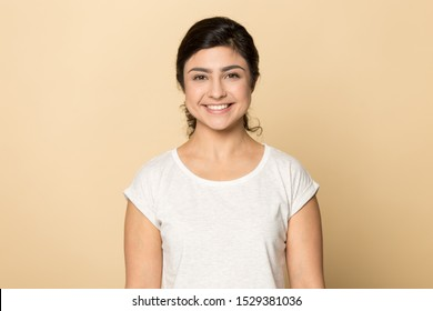 Headshot portrait of smiling millennial indian girl isolated on orange brown studio background look at camera, happy positive young ethnic woman in casual wear posing in white t-shirt showing teeth