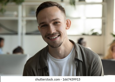 Headshot portrait of smiling millennial male employee talk on video call or web conference in coworking office, profile picture of happy Caucasian young man worker posing in shared workplace