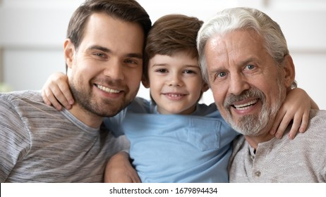 Headshot portrait of smiling three generations of men hug posing for picture together at home, happy little boy embrace young father and elderly grandfather look at camera relax in living room