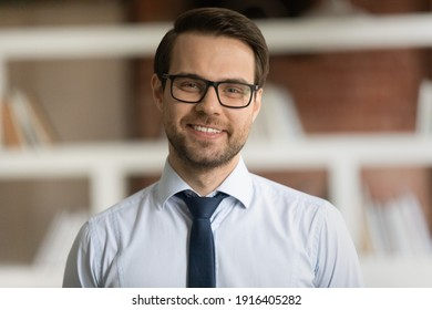Headshot portrait of smiling young Caucasian businessman in suit and glasses pose in office. Profile picture of happy successful male director or CEO show leadership and optimism. Success concept.