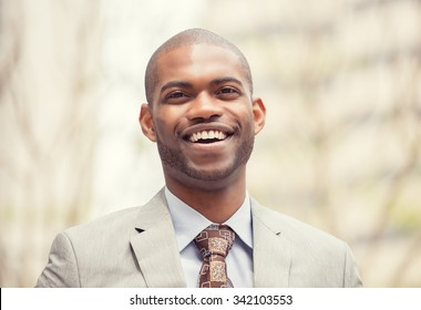 Headshot portrait of young professional man smiling laughing isolated on outside outdoors corporate office background. Positive human emotions feelings facial expressions