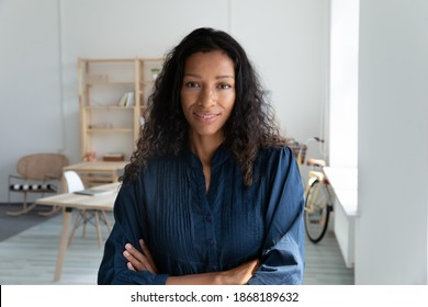 Headshot portrait of young successful African American businesswoman posing in modern office. Profile picture of biracial ethnic female employee at workplace. Recruitment, leadership concept.
