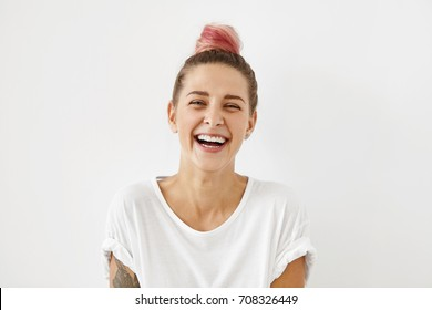 Headshot of positive emotional gorgeous young woman wearing pinkish hair bun grinning broadly, enjoying good day. Beautiful girl with tattoo on arm having fun indoors, laughing at something funny