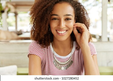 Headshot of positive good looking female with appealing appearance, broad smile, has bushy Afro hairstyle, poses at camera in cafe, rejoices good news. People, emotions and facial expressions
