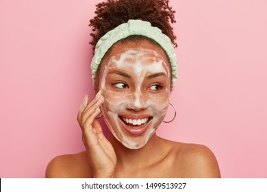 Headshot of pretty dark skinned young model touches cheek with foam, washes face with water and soap, looks gladfully aside, wears round earrings, headband, poses naked against pink background