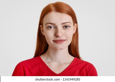 Headshot of pretty freckled redhead female looks with friendly expression at camera, dressed in red sweater, poses against white background, enjoys communication. People and lifestyle concept
