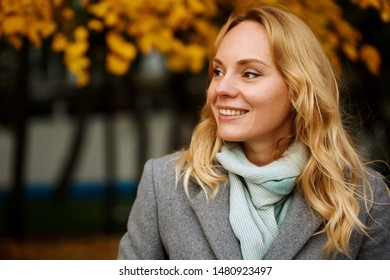 Headshot of pretty smiling blonde woman at the autumn nature with copy space