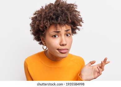 Headshot of puzzled African American woman looks with indignant expressio at camera listens attentively and tries to prove her case has curly hair wears casual jumper poses indoor against white wall