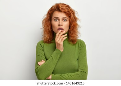 Headshot of puzzled emotive woman keeps hand near opened mouth, has scared look, feels embarrassed and shocked, looks at camera, dressed in green turtleneck, isolated on white wall. Omg concept