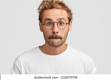 Headshot of puzzled young male presses lips and looks in bewilderment, feels puzzlement, has hesitant expression, contemplates about something, dressed casually, poses against white background