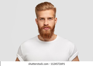 Headshot of red haired serious young male blogger looks confidently at camera, thinks about new content of his web page, dressed casually, earns money distantly, isolated over white background