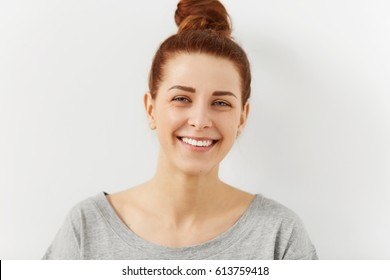 Headshot of relaxed young ginger female hipster with perfect beautiful smile looking with happy expression at camera, rejoicing at her carefree lifestyle, posing indoors against white wall background