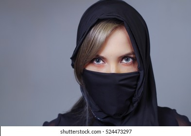 Headshot samurai woman dressed in black with matching veil covering face, facing camera, ninja concept