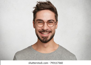 Headshot of satisfied cheerful handsome man grins at camera, glad to find suitable well paid job, isolated over white concrete background. People, positive emotions and facial expressions concept