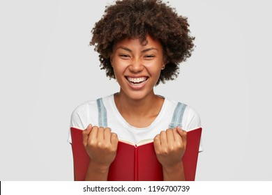Headshot of satisfied dark skinned bookworm happy to finish reading bestseller, holds opened red book in hands, has pleased expression, poses against white background. People and learning concept