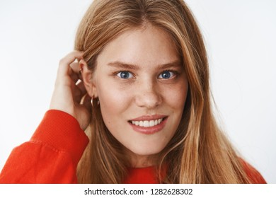 Headshot of sensual and tender charming young woman with fair hair, freckles and blue eyes smiling shy, blushing receiving compliments flicking strand behind ear flirty over grey wall