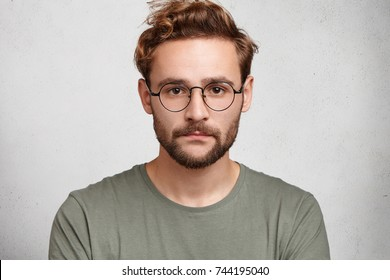 Headshot of serious bearded man with mustache and beard, wears round spectacles, has stylish hairdo, looks confidently, models in white studio, waits for partner. Young student going for classes