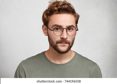 Headshot of serious clever man professor going to conduct lecture, wears spectacles, waits students. Bearded wonk looks confidently, being sure in his knowledge, expresses assertion or self reliance