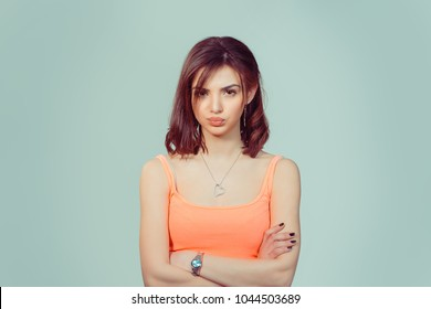 Headshot serious skeptical woman wife looking at you skeptically, doubtful isolated light green yellow studio wall background, pink shirt. Human face expression body language, attitude perception