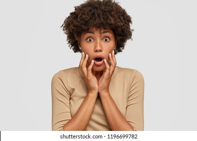 Headshot of shocked beautiful black woman opens mouth widely, keeps both hands on cheeks, cant believe in exciting news, stares with bugged eyes, dressed in beige sweater, isolated on white wall