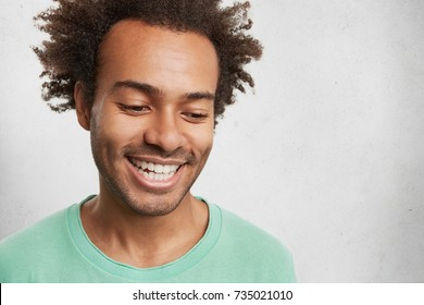 Headshot of shy dark skinned male with crisp hair, smiles broadly, shows white even teeth, looks down, feels embarassed as sees very beautiful woman, wants to make compliment or get acquainted