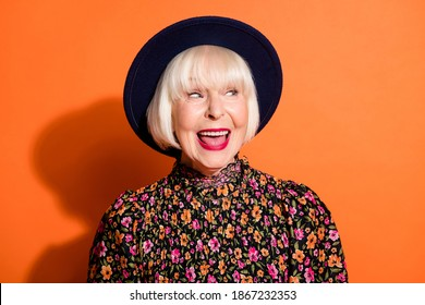 Headshot of sly curious old woman looking blank space smiling red lipstick wearing blouse headwear isolated vivid orange color background