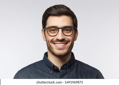Headshot of smiling handsome man with trendy haircut and glasses isolated on gray background