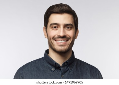 Headshot of smiling handsome man with trendy haircut isolated on gray background
