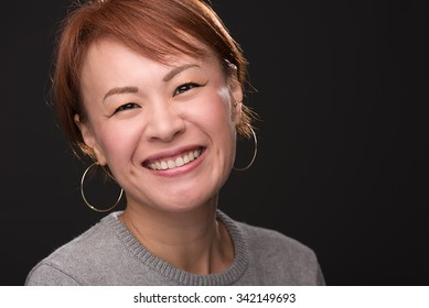 A headshot of a smiling middle aged Japanese woman.