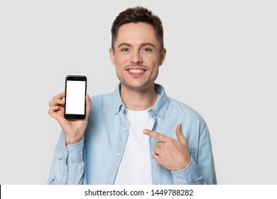 Headshot of smiling millennial man showing at smartphone. Portrait of handsome male pointing with index finger at mock up cellphone, mobile, telephone screen. Technology, gadget, advertisement concept