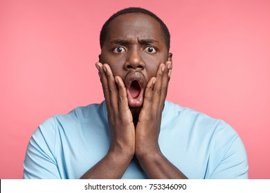 Headshot of stupefied astonished man wears casual t shirt, keeps hands on cheeks, says: Omg, I am tired of that. Surprised African American male realizes his fault. Ethnicity and emotions