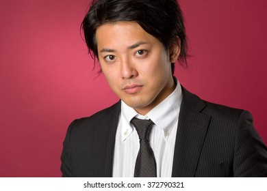 A headshot style portrait of a young Japanese man wearing a business suit with a serious expression on a red background.
