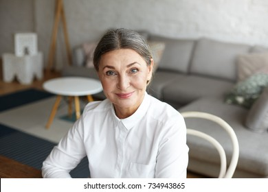 Headshot of successful positive mature 60 year old European woman life coach, consultant or psychologist in formal blouse waiting for client at home office, looking at camera with confident smile