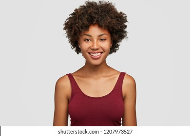 Headshot of successful smiling dark skinned sportswoman, knows how succeed, has toothy smile, dressed in casual vest, expresses good emotions, isolated over white background, feels carefree.