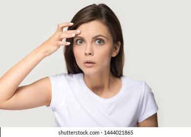 Headshot of surprised millennial woman notice first wrinkles on forehead. Studio portrait of shocked young female looking at camera isolated on gray background. Cosmetology, beauty, skin care concept