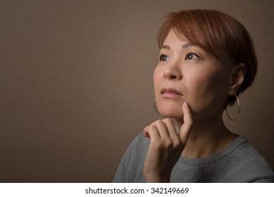 A headshot of a thoughtful middle aged Japanese woman.